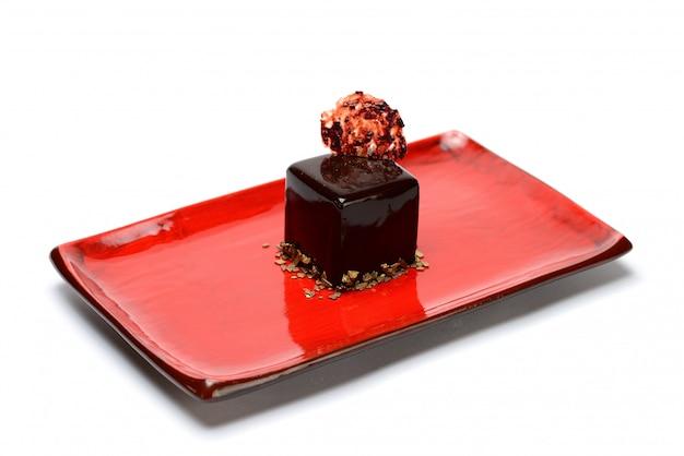 Sobremesa de chocolate em forma de um cubo. em uma placa vermelha