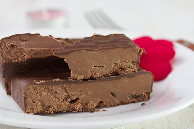 Sobremesa de chocolate no prato branco em madeira branca