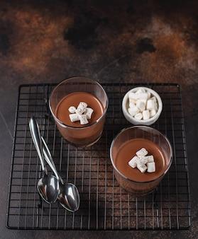 Sobremesa de chocolate (panna cotta, mousse ou pudim) em porções de xícaras de superfície escura, vista lateral