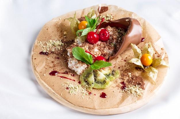 Sobremesa de chocolate planta da mãe com creme e frutas frescas na placa redonda