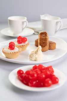 Sobremesa de chrries doces com rodelas de amêndoa e duas cestas de bolos e uma xícara de café e leiteira ao fundo