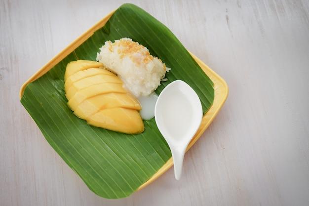Sobremesa de comida asiática manga e arroz pegajoso colocado em folhas de bananeira no prato em ordem