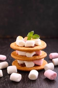 Sobremesa de cookies, chocolate e marshmallow sobre um fundo azul na decoração de natal