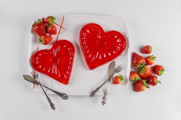 Sobremesa de corações de gelatina doce no prato branco com morango fresco