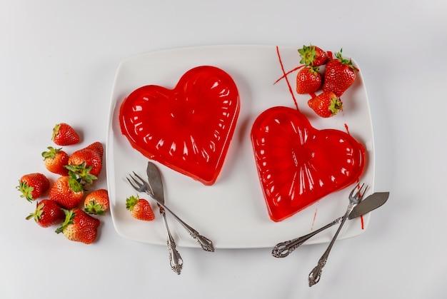 Sobremesa de corações de gelatina doce no prato branco com morangos frescos