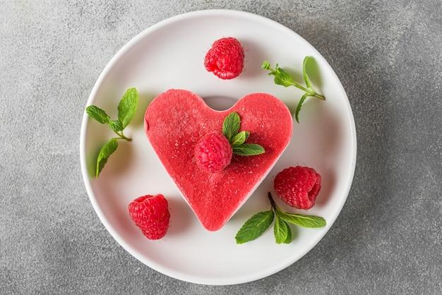 Sobremesa de dia dos namorados. coração em forma de bolo vegan cru vermelho com framboesas e hortelã em um prato. comida deliciosa e saudável