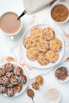 Sobremesa de dois tipos de biscoitos, açúcar de cana e uma xícara de café em um fundo branco.