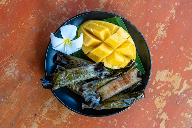 Sobremesa de estilo tailandês, manga amarela com arroz pegajoso de banana em folhas de palmeira. manga amarela e arroz pegajoso é a sobremesa tradicional popular da tailândia. fechar-se