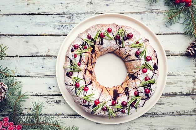 Sobremesa de férias de bolo de natal caseiro tradicional com cranberry e chocolate com decoração de árvore de ano novo no fundo da mesa de madeira vintage. estilo rústico.