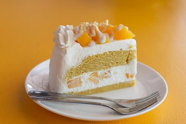 Sobremesa de frutas de verão é cheesecake de manga na mesa amarela
