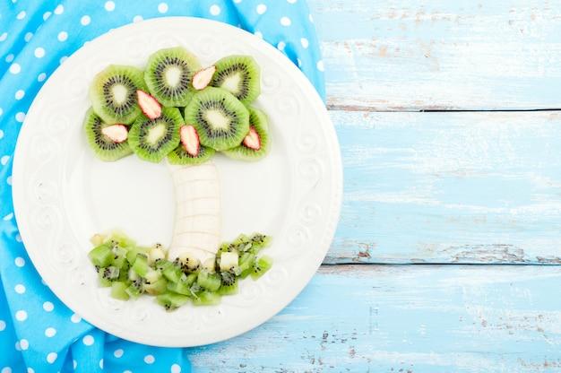 Sobremesa de frutas para crianças com kiwi, banana e morango em fundo de madeira