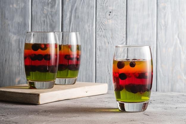 Sobremesa de gelatina com frutas em vidro em uma velha tábua de madeira, pudim doce em camadas colorido