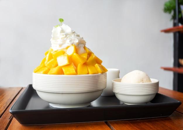Sobremesa de gelo raspado servida com manga fatiada e sorvete de baunilha