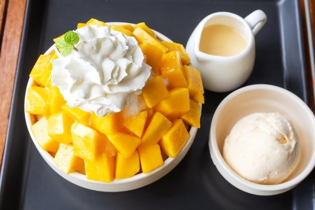 Sobremesa de gelo raspado servido com manga fatiada e sorvete