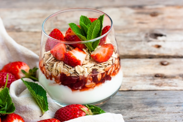 Sobremesa de iogurte de morango com granola em uma mesa de madeira.