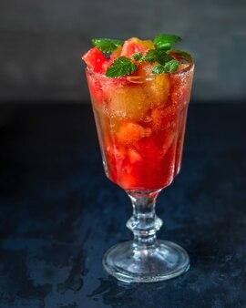 Sobremesa de melancia com água com gás e hortelã em um copo de vidro alto