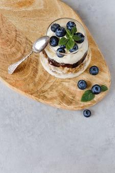 Sobremesa de mirtilo com creme de coalhada e folhas de manjericão cobertura de granola. geléia de mirtilo. vista do topo.