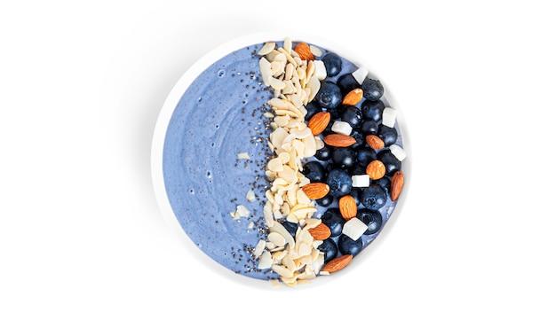 Sobremesa de mirtilo com frutas, sementes de amêndoa e chia isoladas em um fundo branco. tigela de smoothie azul com frutas. foto de alta qualidade