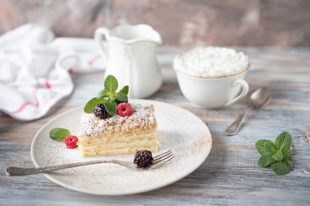 Sobremesa de napoleão em um prato com frutas e hortelã, com uma xícara de cappuccino em uma mesa de madeira.