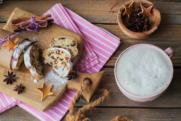 Sobremesa de natal caseira tradicional stollen com frutas secas, nozes e açúcar de confeiteiro em cima fica em uma mesa de madeira rústica