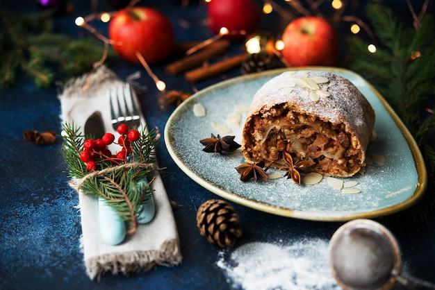 Sobremesa de natal e ano novo. strudel de maçã com luzes do feriado.