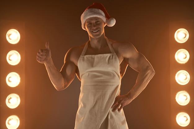 Sobremesa de natal quente sexy musculoso chef vestindo avental e chapéu de papai noel polegar para cima gesto sorrindo, iluminação de lâmpadas e fumaça na cozinha de fundo. dona de casa masculina. marido na cozinha. açougueiro brutal.