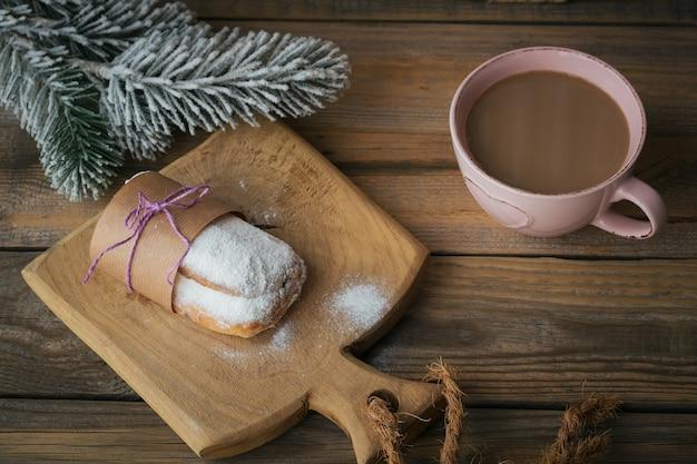 Sobremesa de natal tradicional caseira stollen com frutas secas, nozes e açúcar de confeiteiro em cima fica em uma mesa de madeira rústica