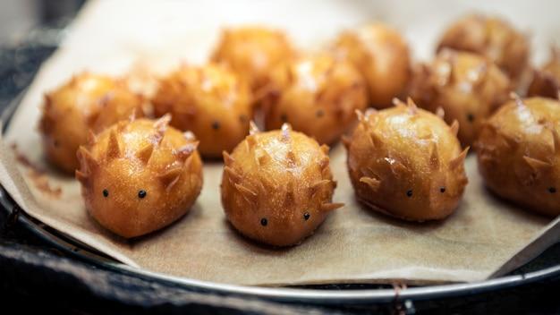 Sobremesa de pastéis de creme em forma de ouriço adorável. bolo japonês com mercado de comida de rua com creme cremoso e espinhoso em barraca à venda em kyoto, japão