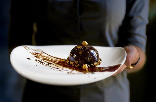 Sobremesa de pastelaria mini mousse francesa em cobertura de chocolate num prato, sobremesa nas mãos de uma garçonete.