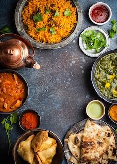 Sobremesa de pratos e aperitivos tradicionais indianos: curry de frango, pilaf, pão naan, samosas, paneer, chutney em fundo rústico. mesa com opção de comida da culinária indiana, espaço para texto