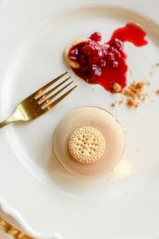 Sobremesa de sorvete com biscoito e geléia de frutas vermelhas elegantemente apresentada com dourado