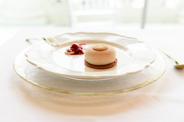 Sobremesa de sorvete com biscoito e geléia de frutas vermelhas elegantemente apresentada com talheres de ouro
