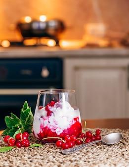 Sobremesa de sorvete com geléia de groselha e frutas frescas. cozinha em segundo plano.