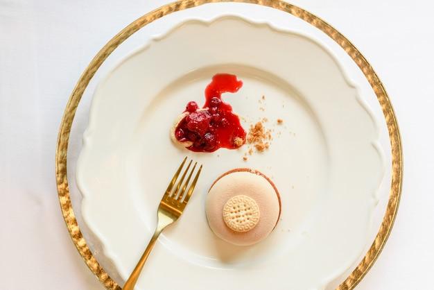 Sobremesa de sorvete elegantemente apresentada com geléia de morango em pratos de luxo e lençóis dourados.