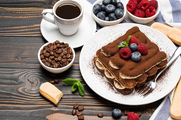 Sobremesa de tiramisu clássico com framboesas e mirtilos e uma xícara de café expresso