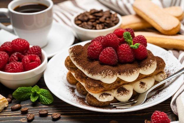 Sobremesa de tiramisu clássico com framboesas e uma xícara de café expresso