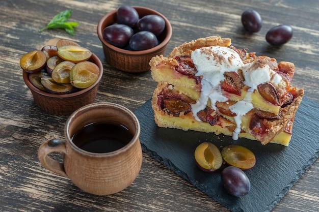 Sobremesa de torta de ameixa orgânica caseira pronta para comer. torta de ameixa com sorvete e xícara de chá quente no fundo de madeira velha, close-up