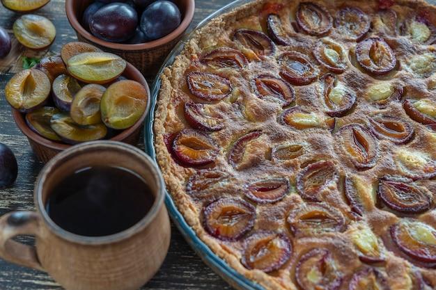 Sobremesa de torta de ameixa orgânica caseira pronta para comer. torta de ameixa e xícara de chá quente no fundo de madeira velho, close-up