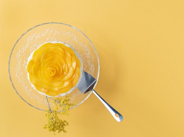 Sobremesa de três leites decorada com pêssegos em fundo amarelo. copie o espaço. vista do topo.