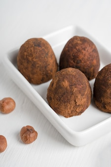 Sobremesa de trufas doces de chocolate orgânico feita de avelã com cacau em pó servida em um prato