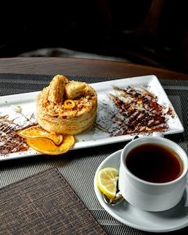 Sobremesa de várias camadas com fatias de laranja e uma xícara de chá