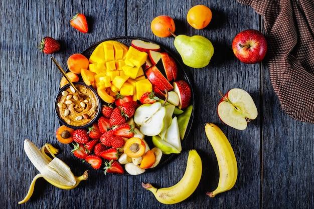 Sobremesa de verão com frutas frescas e morangos com molho de amendoim: morangos, manga tropical, banana, maçãs, peras, damascos e amendoins em uma placa preta sobre uma mesa de madeira escura, vista superior