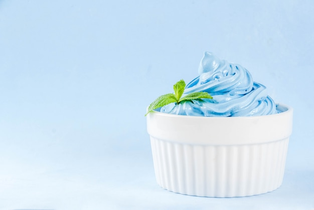Sobremesa de verão dieta saudável, iogurte congelado de baunilha e amora ou sorvete macio em tigelas brancas, isoladas sobre fundo azul claro