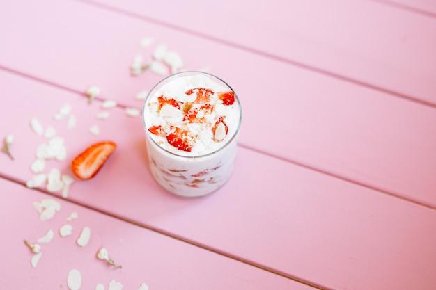 Sobremesa de verão em camadas com morangos, pão de ló e iogurte em um fundo rosa árvore.