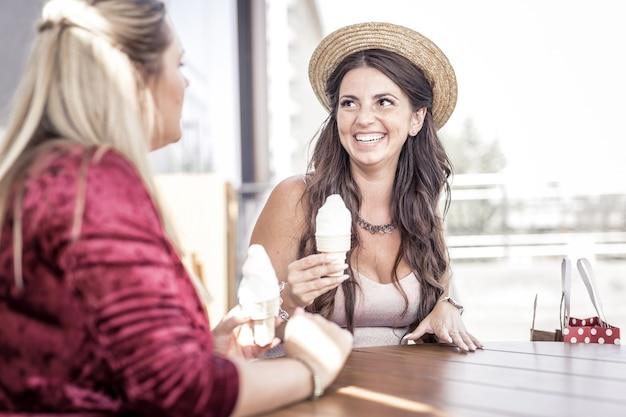Sobremesa de verão. mulheres felizes e positivas rindo umas para as outras enquanto experimentam um sorvete saboroso