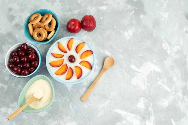Sobremesa de vista superior com frutas fatiadas frutas dentro da placa, juntamente com bolachas doces frutas frescas em branco
