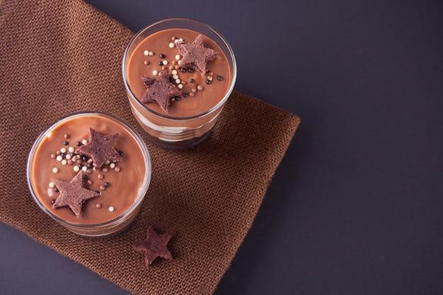 Sobremesa do chocolate nos frascos de vidro em uma tabela com colher de madeira. vista do topo.