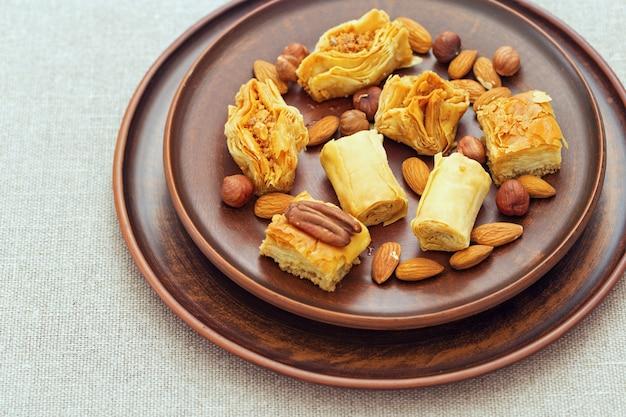 Sobremesa do oriente médio com calda de mel e nozes picadas em uma placa redonda plana de barro. os doces tradicionais do mel fecham-se acima. foco seletivo.