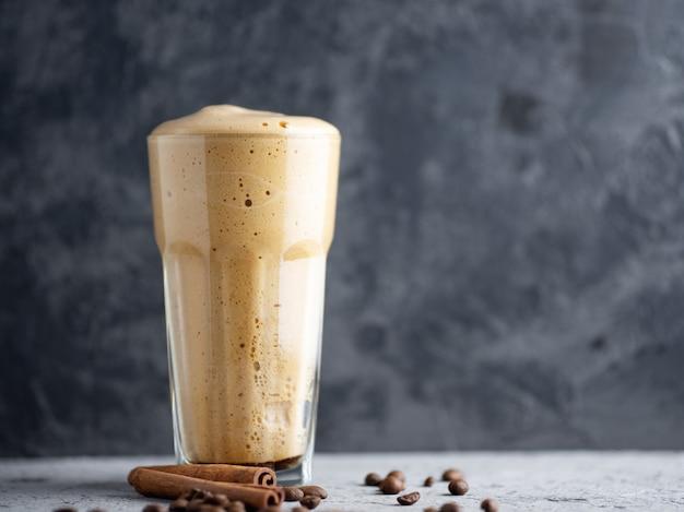 Sobremesa doce e deliciosa de café instantâneo batido em um copo de vidro