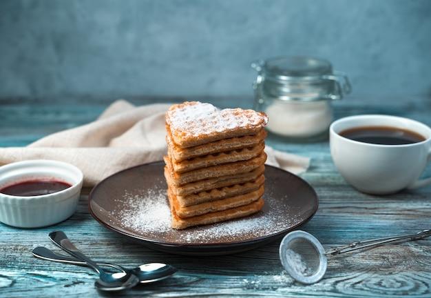 Sobremesa doce e waffles com açúcar de confeiteiro e baunilha em um fundo de madeira cinza-azulado.
